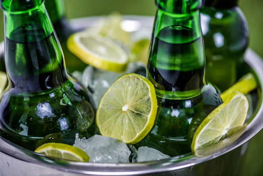 bucket with ice cubes, beer bottles and lemon slices